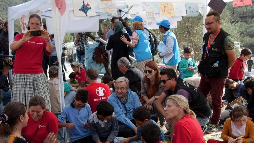 "United Nations High Commissioner for Refugees Antonio Guterres, center, sits between migrants and refugees at the Moria camp on the eastern Aegean island of Lesbos, Greece, Saturday Oct. 10, 2015. Greece's first ""hotspot,"" or migrant processing center, will open over the next 10 days, allowing migrants to be flown to other European Union countries, mostly of their preference, and have their asylum applications processed there, European Union officials say.  (AP Photo/Antonis Pasvantis)"