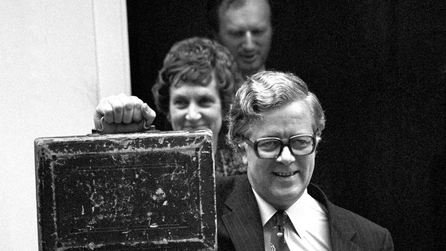 FILE In this June 12, 1970 file photo, Britain's Chancellor of the Exchequer,  Geoffrey Howe, lifts the familiar red budget box, as he leaves No 11 Downing Street to present his first budget with his wife Elspeth, in the background. The family of Britain's former Treasury chief Geoffrey Howe says the longtime Conservative Party figure has died at his home. He was 88. The family said Saturday that he had died suddenly of a suspected heart attack late Friday night, Oct. 9, 2015,  at his home in Warwickshire, north of London.  (PA via AP, File) UNITED KINGDOM OUT NO SALES NO ARCHIVE