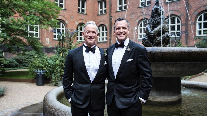 """The American ambassador in Denmark Rufus Gifford, right, smiles beside his partner Stephen DeVincent after they got married at Copenhagen City Hall in Copenhagen on Saturday, Oct. 10 2015.  The U.S. ambassador to Denmark has married his partner in the Scandinavian country that became the first nation to allow gay couples to formalize their unions in 1989. Rufus Gifford, the U.S. envoy since September 2013, is a strong gay rights advocate and often appears with Stephen DeVincent, a 56-year-old veterinarian, at his side. The two were married Saturday at the Copenhagen City Hall. Gifford, a 41-year-old Boston native, wrote on Twitter: """"26 yrs ago the site of 1st legal gay unions in the world. Humbled and emotional."""" (Rasmus Flindt Pedersen/Polfoto via AP)  DENMARK OUT"""