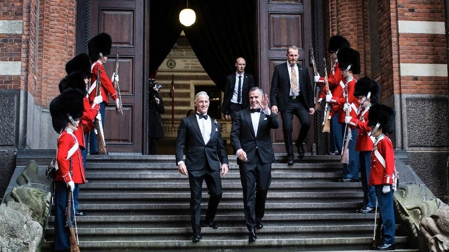 """The American ambassador in Denmark Rufus Gifford, right, waves next to his partner Stephen DeVincent after they got married at Copenhagen City Hall in Copenhagen on Saturday, Oct. 10 2015.  The U.S. ambassador to Denmark has married his partner in the Scandinavian country that became the first nation to allow gay couples to formalize their unions in 1989. Rufus Gifford, the U.S. envoy since September 2013, is a strong gay rights advocate and often appears with Stephen DeVincent, a 56-year-old veterinarian, at his side. The two were married Saturday at the Copenhagen City Hall. Gifford, a 41-year-old Boston native, wrote on Twitter: """"26 yrs ago the site of 1st legal gay unions in the world. Humbled and emotional."""" (Rasmus Flindt Pedersen/Polfoto via AP)  DENMARK OUT"""