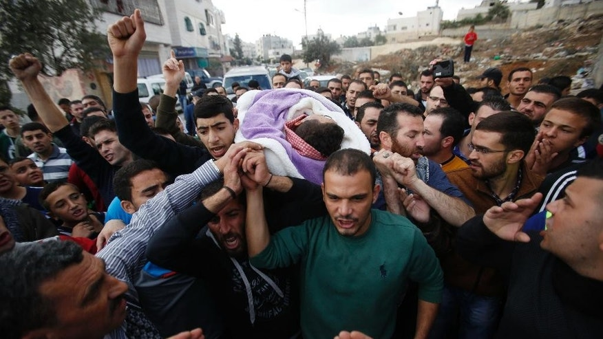Palestinians carry the body of Mohammed al-Jaabari during his funeral in Hebron Saturday, Oct. 10, 2015.  al-Jaabari was killed after he attacked an Israeli policeman outside Kiryat Arba settlement Friday, according to Israeli police.  (AP Photo/Nasser Shiyoukhi)