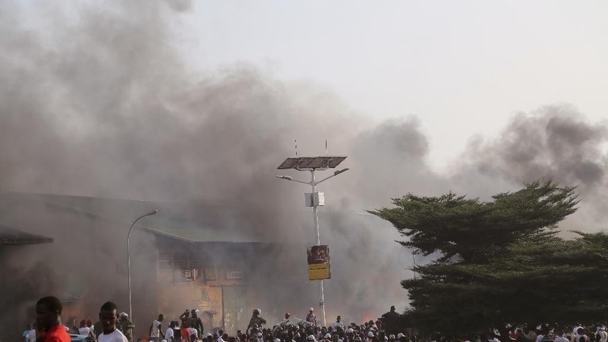 In this photo taken Thursday, Oct. 8, 2015, smoke rises from a local market during a political rally in support of  UFDG presidential candidate Cellou Dalein Diallo in the city of  Guinea  Conakry, Guinea.  Political clashes between the opposition and ruling party in Guinea are setting the stage for the country's second democratic election in more than half a century. The international community watches the West African country, unable to shake the deadly Ebola virus, with concern that ethnic and political tensions brought to the surface in past elections haven't declined in the past five years.  (AP Photo/ Youssouf Bah)