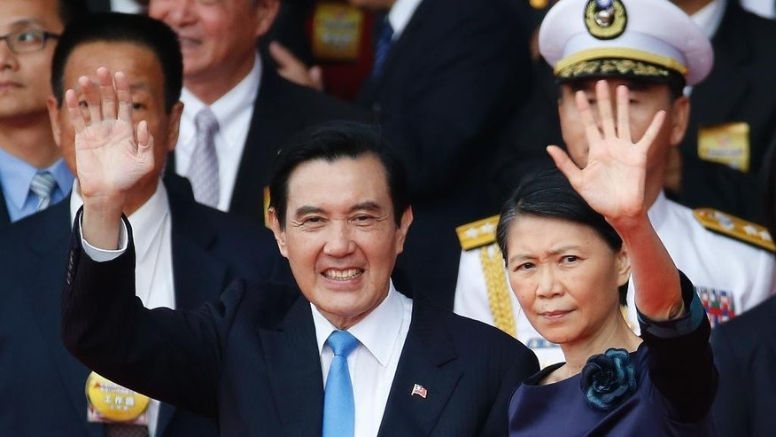 Taiwan's President Ma Ying-jeou, left, and his wife Chow Mei-ching wave to attendants during the National Day celebrations in Taipei, Taiwan, Saturday, Oct. 10, 2015. Ma warned his successor Saturday to continue to meet Beijing's condition for dialogue that the two sides see each other as parts of one country, despite growing discontent at home toward the mainland's Communist leadership. (AP Photo/Wally Santana)
