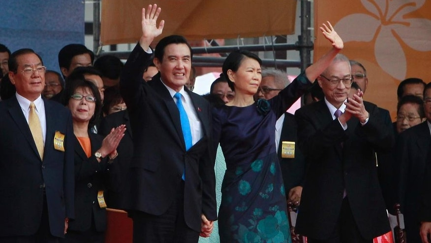 Taiwan's President Ma Ying-jeou and his wife Chow Mei-ching wave to attendants during the National Day celebrations in Taipei, Taiwan, Saturday, Oct. 10, 2015. Ma warned his successor Saturday to continue to meet Beijing's condition for dialogue that the two sides see each other as parts of one country, despite growing discontent at home toward the mainland's Communist leadership. (AP Photo/Chiang Ying-ying)