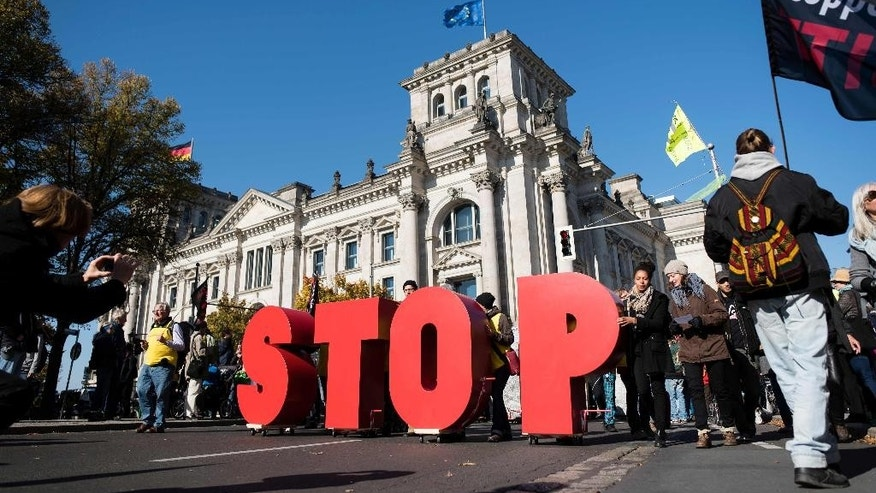Demonstrators hold the letters 'STOP' as they attend a demonstration against the free trade agreements TTIP (Transatlantic Trade and Investment Partnership) and CETA (Comprehensive Economic and Trade Agreement) in front of the Reichstag building in Berlin, Germany, Saturday, Oct. 10, 2015. (Gregor Fischer/dpa via AP)