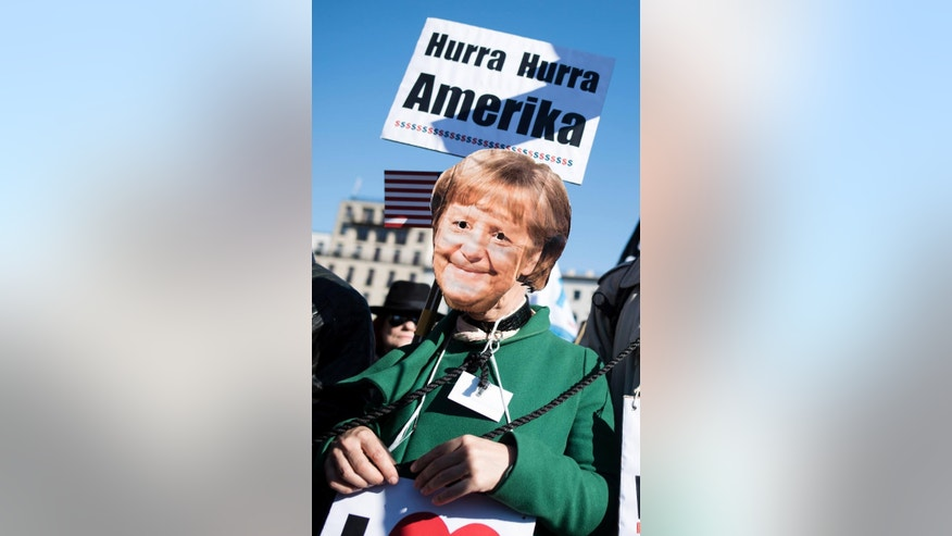 A demonstrator wears a mask with a picture of German Chancellor Angela merkel as he attends a demonstration against the free trade agreements TTIP (Transatlantic Trade and Investment Partnership) and CETA (Comprehensive Economic and Trade Agreement) in front of the Brandenburg Gate in Berlin, Germany, Saturday, Oct. 10, 2015. (Gregor Fischer/dpa via AP)