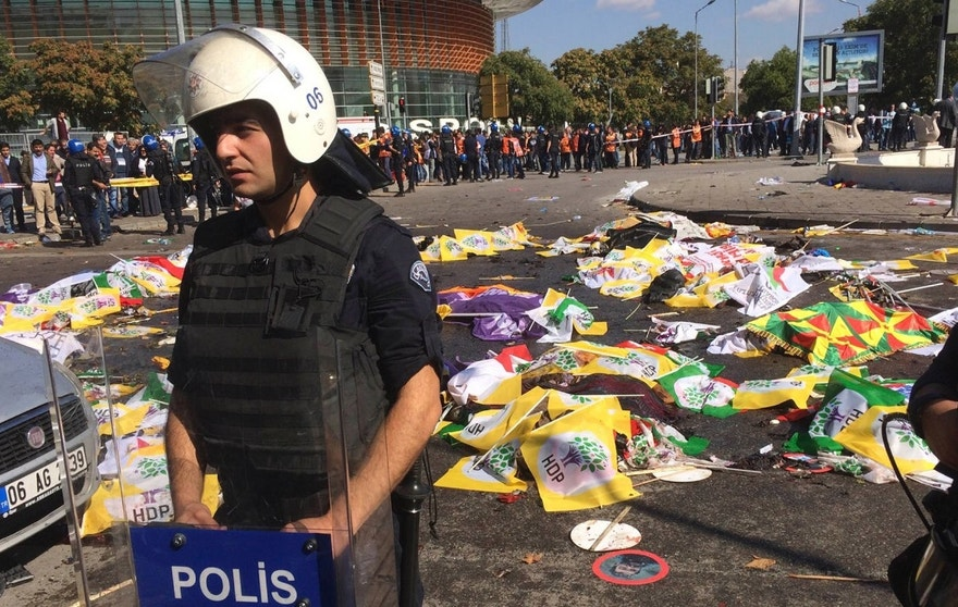 Oct. 10, 2015: Bodies of victims are covered with flags and banners as a police officer secure the area after an explosion in Ankara, Turkey.