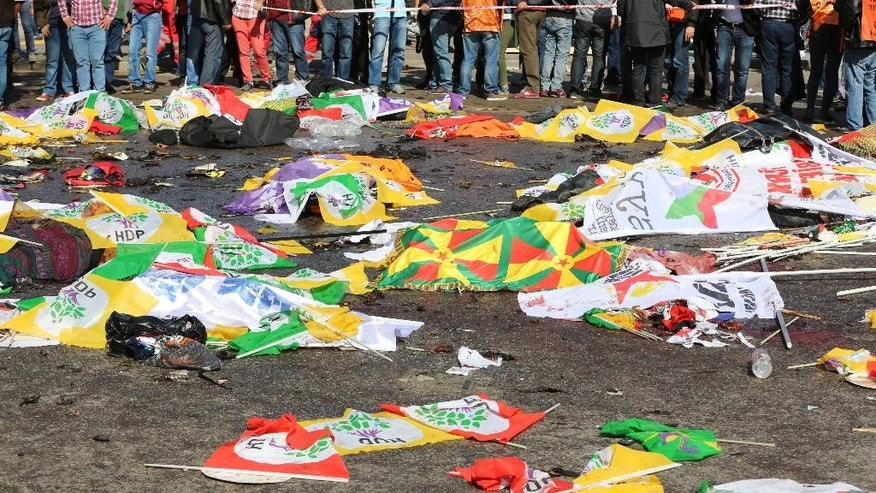 Bodies of victims are covered with flags and banners at the site of an explosion in Ankara, Turkey, Saturday, Oct. 10, 2015. Turkey's health minister says two bomb explosions in the Turkish capital have killed scores of people. The explosions occurred minutes apart near Ankara's main train station as people were gathering for a rally, organized by the country's public sector workers' trade union and other civic society groups. The rally aimed to call for an end to the renewed violence between Kurdish rebels and Turkish security forces. (AP Photo/Burhan Ozbilici)