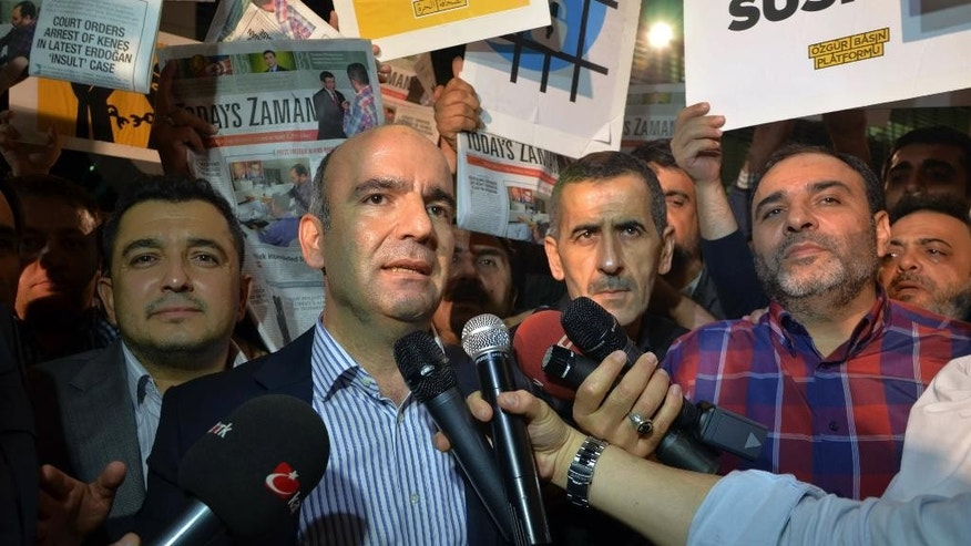 "Abdulhamit Bilici, editor-in-chief of Zaman newspaper, speaks to the media minutes before police detain Bulent Kenes, editor-in-chief of Today's Zaman, right, in his office in Istanbul, Turkey, late Friday, Oct. 9, 2015. Police have detained the chief editor of opposition English-language newspaper for posting a series of tweets critical of President Recep Tayyip Erdogan. Kenes was taken away from the newspaper's headquarters in Istanbul on Friday, as several supporters chanted: ""Free media cannot be silenced!"" The detention was televised live.(AP Photo/Isa Simsek, Zaman)"