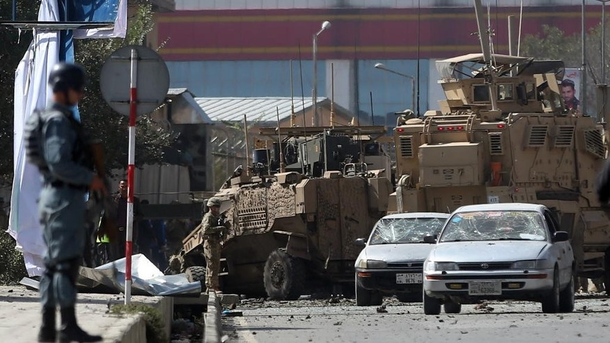 Afghan and foreign soldiers inspect the site of a bomb attack that targeted several armored vehicles belonging to forces attached to the NATO Resolute Support Mission, in downtown of Kabul, Afghanistan, Sunday, Oct. 11, 2015. Gen. Abdul Rahman Rahimi, the Kabul city police chief, said that three Afghan civilians were wounded in the attack that damaged one of the vehicles but caused no fatalities. (AP Photo/Massoud Hossaini)