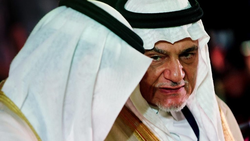 "In this Saturday, Oct. 10, 2015 photo, Prince Turki al-Faisal talks with one of the dignitaries during the opening day of the Beirut Institute Summit in Abu Dhabi, United Arab Emirates. The prince, who spoke to The Associated Press in an interview Sunday during a visit to Abu Dhabi, said the oversight and management of the annual Islamic hajj pilgrimage is ""a matter of sovereignty"" and ""privilege"" and will not be shared with other nations. (AP Photo/Kamran Jebreili)"