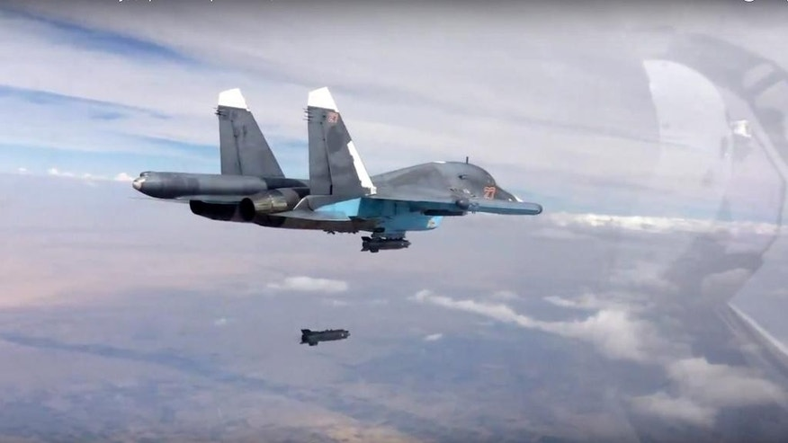 In this photo made from the footage taken from Russian Defense Ministry official web site on Friday, Oct. 9, 2015, a bomb is released from Russian Su-34 strike fighter in Syria. Activists report intense fighting between insurgents and Syrian troops in the country's center amid new territorial gains for the government, backed by Russian airstrikes. (Russian Defense Ministry Press Service via AP)