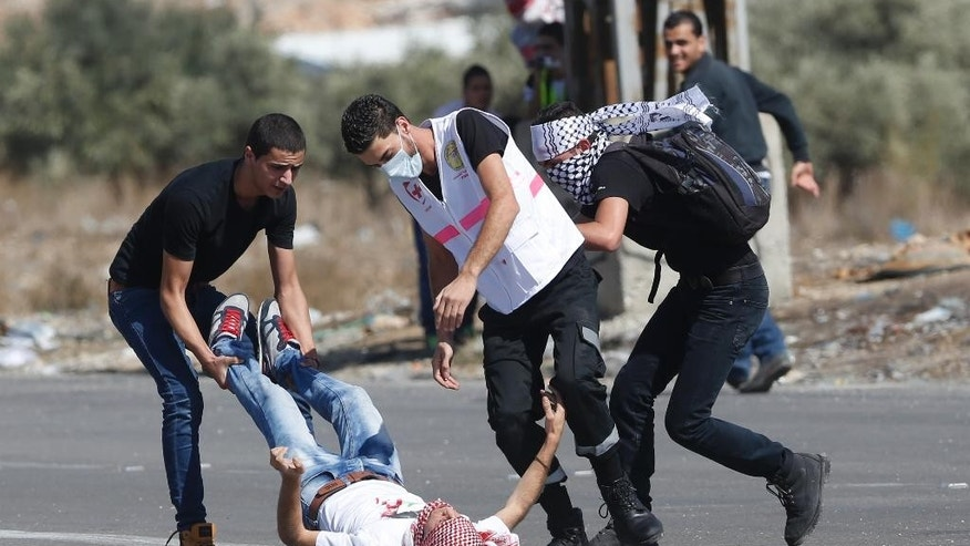 An injured Palestinian demonstrator is helped during clashes at the Hawara checkpoint near of the West Bank city of Nablus, Sunday, Oct. 11, 2015. Tensions in he West Bank continued with near-daily violent demonstrations. At least 45 Palestinians were wounded by live bullets in clashes between university students and Israeli forces at the military checkpoint near Nablus on Sunday, the Palestinian Health Ministry said. (AP Photo/Nasser Shiyoukhi)