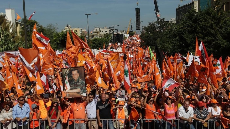 Supporters of Christian leader Michel Aoun hold Free Patriotic Movement and Lebanese flags and pictures of him during a rally near the empty presidential palace in the Beirut suburb of Baabda, Lebanon, Sunday, Oct. 11, 2015. Aoun, who is bidding for the presidency, is pressing the country's political elite to pass a parliamentary electoral law and elect a president. The large rally Sunday comes amid a persistent political stalemate in Lebanon, which has had no president for over a year and a parliament torn by political rivalry. (AP Photo/Hassan Ammar)