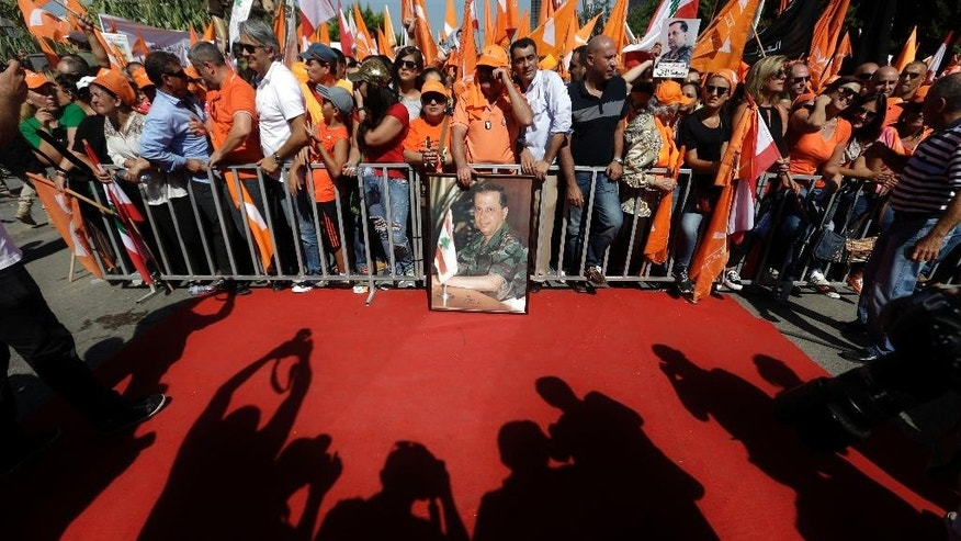 Supporters of Christian leader Michel Aoun hold Free Patriotic Movement and Lebanese flags during a rally near the empty presidential palace in the Beirut suburb of Baabda, Lebanon, Sunday, Oct. 11, 2015. Aoun, who is bidding for the presidency, is pressing the country's political elite to pass a parliamentary electoral law and elect a president. The large rally Sunday comes amid a persistent political stalemate in Lebanon, which has had no president for over a year and a parliament torn by political rivalry. (AP Photo/Hassan Ammar)