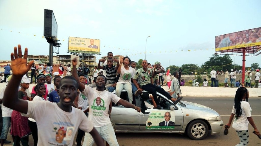 In this photo taken Thursday, Oct. 8, 2015,  thousands of supporters of UFDG presidential candidate Cellou Dalein Diallo cheer in a street during a political rally in the city of  Conakry, Guinea. Political clashes between the opposition and ruling party in Guinea are setting the stage for the country's second democratic election in more than half a century. The international community watches the West African country, unable to shake the deadly Ebola virus, with concern that ethnic and political tensions brought to the surface in past elections haven't declined in the past five years. (AP Photo/Youssouf Bah)