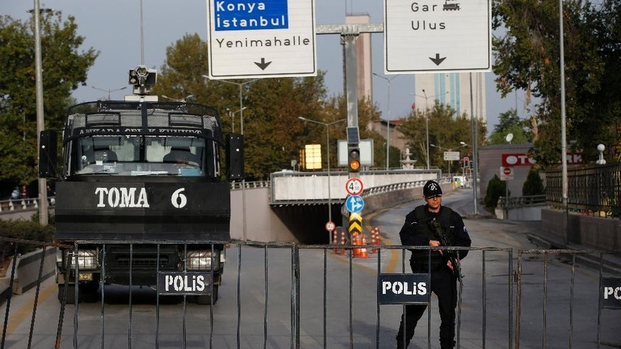 Turkish police block the way to the site of Saturday's explosions in Ankara, Turkey, Sunday, Oct. 11, 2015. Scuffles broke out as police prevented pro-Kurdish politicians and other mourners from laying carnations at the site of two suspected suicide bombings. Police insisted investigators were still working at the site. (AP Photo/Emrah Gurel)