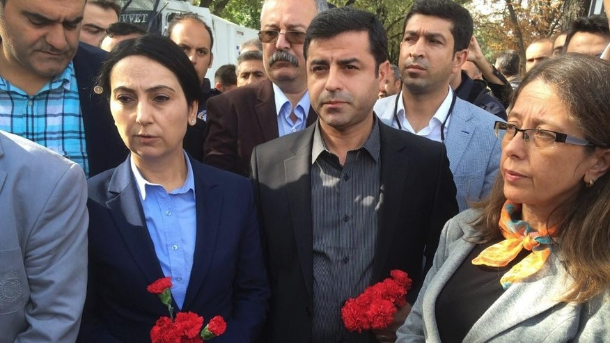 Selahattin Demirtas, center, and Figen Yuksekdag, left, co-leaders of the pro Kurdish Democratic Party of Peoples (HDP) hold carnations in Ankara, Turkey, Sunday Oct. 11, 2015, as they with other members of the party's delegation and mourners that were planning to hold a memorial for the victims at the site of Saturday's explosions are held back by police. Scuffles broke out as police prevented pro-Kurdish politicians and other mourners from laying carnations at the site of two suspected suicide bombings. Police insisted investigators were still working at the site. (AP Photo/Burhan Ozbilici)