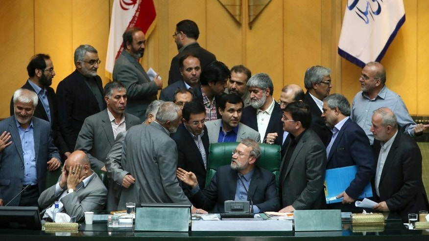 Iran's parliament speaker Ali Larijani, center, speaks with lawmakers in an open session of parliament while discussing a bill on Iran's nuclear deal with world powers, in Tehran, Iran, Sunday, Oct. 11, 2015. Iran's official IRNA news agency reported Sunday the country's parliament has approved an outline of a bill that allows the government to implement a historic nuclear deal reached between Iran and world powers. (AP Photo/Ebrahim Noroozi)
