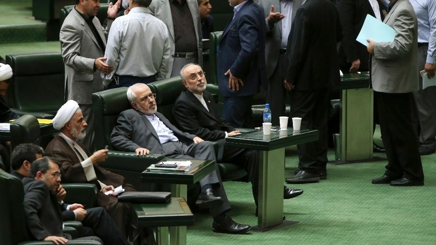 Foreign Minister Mohammad Javad Zarif, one of Iran's top nuclear negotiators, seated at second right, and head of Iran's Atomic Energy Organization Ali Akbar Salehi, seated at right, attend an open session of parliament while discussing a bill on Iran's nuclear deal with world powers, in Tehran, Iran, Sunday, Oct. 11, 2015. Iran's official IRNA news agency reported Sunday the country's parliament has approved an outline of a bill that allows the government to implement a historic nuclear deal reached between Iran and world powers. (AP Photo/Ebrahim Noroozi)