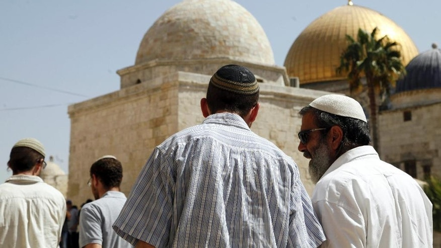 In this Thursday, July 28, 2015 photo, a group of religious Jews walk in front of the Dome of the Rock in Jerusalem. Jewish and Muslim activists, self-declared defenders of their faiths, have become more organized in the contest over a sprawling Jerusalem hilltop shrine that is central to both religions and triggered new Israeli-Palestinian violence in recent weeks. (AP Photo/Mahmoud Illean)