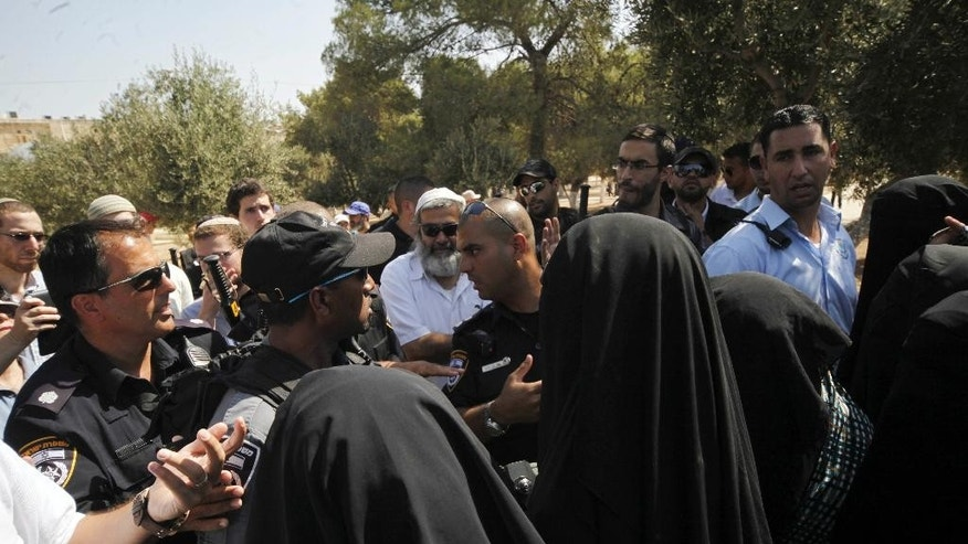 In this Thursday, July 28, 2015 photo, Palestinian women confront a group of religious Jews escorted by Israeli police at the Al-Aqsa compound in Jerusalem. Jewish and Muslim activists, self-declared defenders of their faiths, have become more organized in the contest over a sprawling Jerusalem hilltop shrine that is central to both religions and triggered new Israeli-Palestinian violence in recent weeks. (AP Photo/Mahmoud Illean)