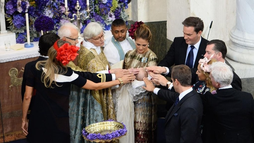 Sweden's Princess Madeleine holds her son Prince Nicolas, at centre with her husband,  Christopher O'Neil at background right, as they stand at the font during the christening ceremony of Prince Nicolas, at the Drottningholm Palace Church, near  Stockholm, Sweden, Sunday, Oct. 11, 2015.  The son of Sweden's Princess Madeleine and New York banker Christopher O'Neill has been baptized near Stockholm. Prince Nicolas Paul Gustaf, also to be known as the Duke of Angermanland after a province in northern Sweden, is the first grandson of King Carl XVI Gustaf, who has two granddaughters. Nicolas was born on June 15 in Stockholm. Standing from left are Countess Natascha Abensperg, Prince Carl Philip, first preacher of the Court Lars-Goran Lonnermark, Arch Bishop Antje Jackelen, pastor Michael Bjerkhagen, Unidentified godparents at right.  (Maja Suslin/TT News Agency via AP)  SWEDEN OUT