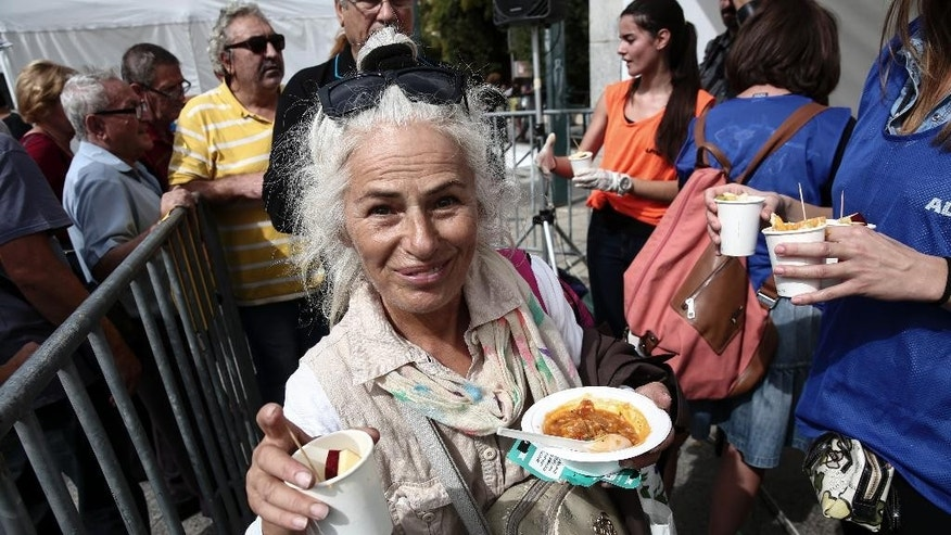 A woman is served fruits and a meal made with 'wasted' produce deemed unsuitable by food stores because of their appearance, during an event against food waste, in Athens, Greece, Sunday Oct. 11, 2015. The event was part of the 'Feeding5000' campaign which aims to highlight the waste of foodstuff in advanced societies.   (AP Photo/Yorgos Karahalis)