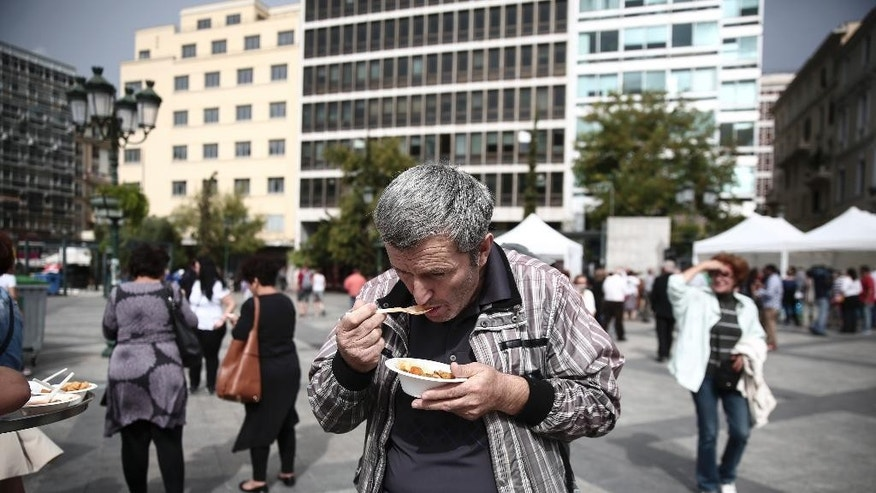 A man eats a meal made with 'wasted' produce deemed unsuitable by food stores because of their appearance, during an event against food waste, in Athens, Greece, Sunday Oct. 11, 2015. The event was part of the 'Feeding5000' campaign which aims to highlight the waste of foodstuff in advanced societies.   (AP Photo/Yorgos Karahalis)