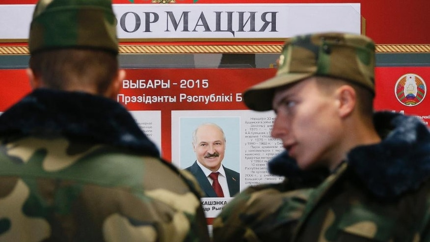 Belarusian army soldiers examine a candidates list with a portrait of Belarusian President Alexander Lukashenko at a polling station during presidential elections in Minsk, Belarus, Sunday, Oct. 11, 2015. (AP Photo/Dmitry Lovetsky)