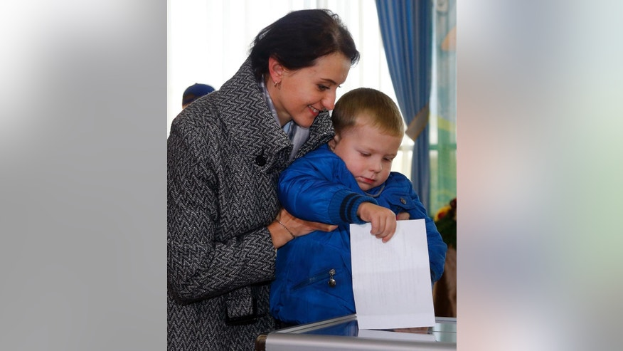 A Belarusian woman with her son casts a ballot at a polling station during presidential elections in Minsk, Belarus, Sunday, Oct. 11, 2015. (AP Photo/Sergei Grits)