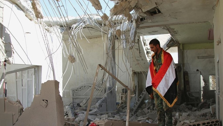 In this photo taken on Sunday, Oct. 11,  2015, a Syrian soldier wrapped in a Syrian flag stands in a damaged house in Achan, Hama province, Syria. Russian jets intensified their airstrikes Monday in the central Syrian province as government and allied troops pushed out insurgents from local villages to expand their control of the area, activists and a military statement said. (Alexander Kots/Komsomolskaya Pravda via AP)