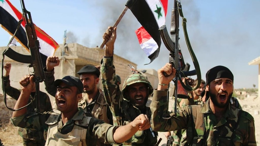 In this photo taken on Sunday, Oct. 11, 2015, Syrian soldiers waving Syrian flags celebrate the ?apture of Achan, Hama province, Syria. Russian jets intensified their airstrikes Monday in the central Syrian province as government and allied troops pushed out insurgents from local villages to expand their control of the area, activists and a military statement said. (Alexander Kots/Komsomolskaya Pravda via AP)