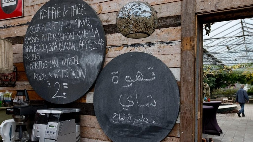 A worker in a garden center passes, rear, while a sign in arabic in the bar area is seen in the village of Oranje, Netherlands, Thursday, Oct. 8, 2015,whose local population of 130 is overwhelmingly outnumbered by hundreds of migrants.  In this tiny Dutch village, Jan Voortman's garden center has added some new products to its lineup of plants, seeds and wooden clogs: falafel, couscous and water pipes. The enterprising store owner is capitalizing on the newest residents of rural Oranje, until recently population 130: Hundreds of asylum seekers from as far away as Syria, Sudan and Eritrea who are being housed in a disused vacation camp. But the resolutely cheerful Voortman sees his fellow townspeople adopting a starkly different attitude. (AP Photo/Peter Dejong)