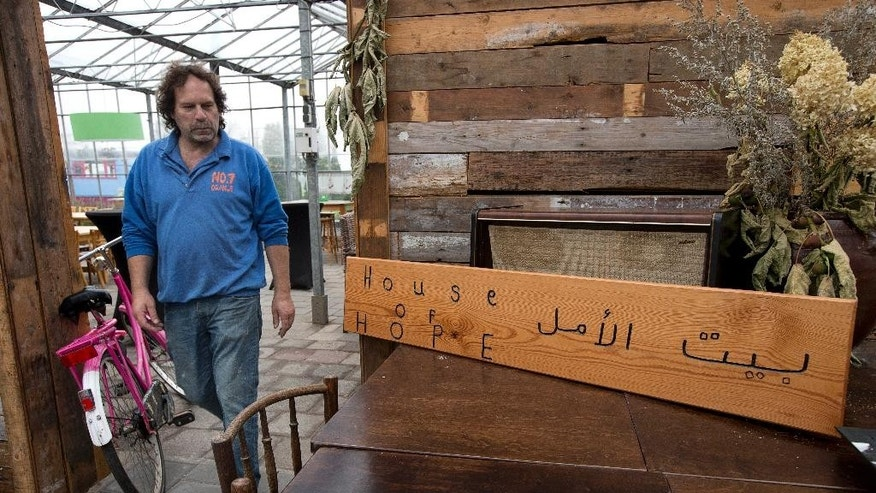 Jan Voortman passes a sign reading House of Hope in english and arabic as he finishes cleaning up the bar area in his garden center in the village of Oranje, Netherlands, Thursday, Oct. 8, 2015, whose local population of 130 is overwhelmingly outnumbered by hundreds of migrants.  In this tiny Dutch village, Jan Voortman's garden center has added some new products to its lineup of plants, seeds and wooden clogs: falafel, couscous and water pipes. The enterprising store owner is capitalizing on the newest residents of rural Oranje, until recently population 130: Hundreds of asylum seekers from as far away as Syria, Sudan and Eritrea who are being housed in a disused vacation camp. But the resolutely cheerful Voortman sees his fellow townspeople adopting a starkly different attitude. (AP Photo/Peter Dejong)