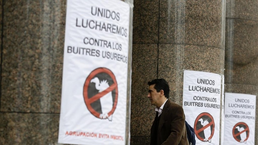 "FILE - In this July 29, 2014, file photo, a man walks by signs posted at the entrance of the Argentine Economy Ministry reading in Spanish; ""Together we will fight against the loan shark vultures,"" referring to an unresolved dispute over $1.5 billion in unpaid debts after its record $100 billion default in 2001, known locally as ""vulture funds,"" in Buenos Aires, Argentina. Like a dark cloud, the bitter fight between Argentina and a group of holdout creditors in the U.S. has hung over South America's second largest economy for years, preventing the country from accessing international credit market. (AP Photo/Victor R. Caivano,File)"