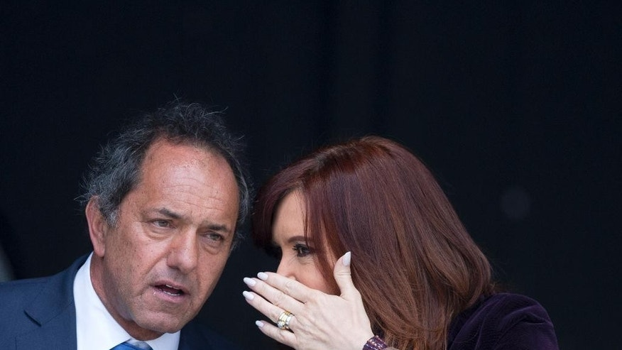 FILE - In this Sept. 9, 2015, file photo, Daniel Scioli, governor of Buenos Aires province and presidential hopeful, left, listens to Argentina's President Cristina Fernandez at the inauguration of a heath center in the suburbs of Buenos Aires, Argentina. Scioli, who leads in the polls, has taken up Fernandez's hard line against the hedge funds that hold $1.5 billion of Argentine debt, yet he is also promising to find a solution. Economists on his team have made clear that Argentina will have problems raising money until the dispute is settled. (AP Photo/Natacha Pisarenko, File)