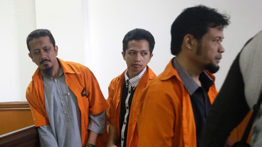 Suspected militants, from left, Abdul Hakim, Ahmad Junaedi and Tuah Febriwansyah, who is also known as Fachry, attend trial at West Jakarta District Court in Jakarta, Indonesia, Monday, Oct. 12, 2015. The Indonesians along with four other fellow countrymen went on trial Monday on charges of conspiring with terrorists and recruiting for militant groups in the Mideast, including the Islamic State, which has an estimated hundreds of Indonesians as members. (AP Photo/Tatan Syuflana)