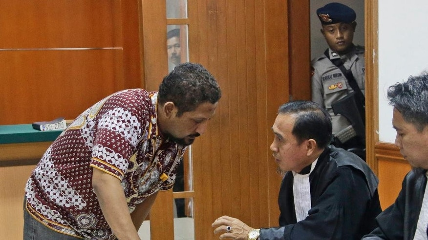 Suspected militant Ridwan Sungkar, left, consults with his lawyer Ashluddin Hatjani during his trial hearing at West Jakarta District Court in Jakarta, Indonesia, Monday, Oct. 12, 2015. The Indonesian, along with six other fellow countrymen went on trial Monday on charges of conspiring with terrorists and recruiting for militant groups in the Mideast, including the Islamic State, which has an estimated hundreds of Indonesians as members. (AP Photo/Tatan Syuflana)
