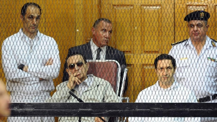 FILE - In this Sept. 14, 2013 file photo, former Egyptian President Hosni Mubarak, seated center left, and his two sons, Gamal Mubarak, left, and Alaa Mubarak attend a hearing in a courtroom in Cairo, Egypt. An Egyptian court on Monday, Oct. 12, 2015, has ordered the release of the sons of deposed autocrat Hosni Mubarak, Gamal, Mubarak's one-time heir apparent, and his brother Alaa, a wealthy businessman, after time served on a corruption conviction.  Their father remains held in a military hospital. (AP Photo/Mohammed al-Law, File)