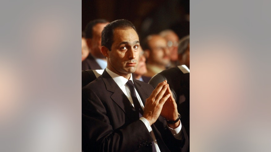FILE  - In this Jan. 6, 2005 file photo, Gamal Mubarak attends a midnight Christmas mass at the Coptic Orthodox Church. An Egyptian court on Monday, Oct. 12, 2015, has ordered the release of the sons of deposed autocrat Hosni Mubarak, Gamal, Mubarak's one-time heir apparent, and his brother Alaa, a wealthy businessman, after time served on a corruption conviction. The two were first detained in April 2011 — two months after their father stepped down during the popular uprising against him, but were later released before being convicted last summer. Their father remains held in a military hospital. (AP Photo/Amr Nabil, File)