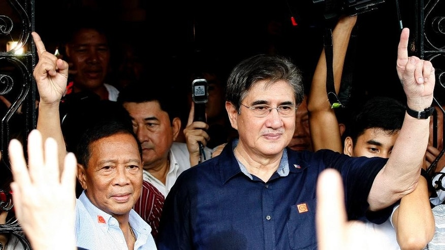 "Philippine Vice-President and now presidential candidate Jejomar Binay, left, and running mate Senator Gregorio ""Gringo"" Honasan flash the No. 1 signs as they emerge from the Commission on Elections after filing their respective certificates of candidacy for next year's presidential elections Monday, Oct. 12, 2015 in Manila, Philippines. Binay and Honasan were the first candidates to file their candidacy before the Commission on Elections. (AP Photo/Bullit Marquez)"