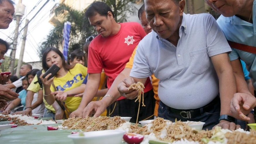"Philippine Vice-President and now presidential candidate Jejomar Binay, second from right, eats breakfast known as ""boodle fight"" with informal settlers prior to filing his certificate of candidacy for next year's presidential elections Monday, Oct. 12, 2015 in Manila, Philippines. Binay and running mate Gregorio ""Gringo"" Honasan were the first candidates to file their candidacy before the Commission on Elections. (AP Photo/Bullit Marquez)"