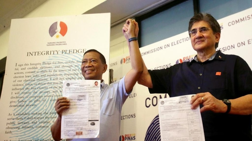 "Philippine Vice-President and now presidential candidate Jejomar Binay, left, and running mate Senator Gregorio ""Gringo"" Honasan show their respective certificates of candidacy at the start of the weeklong filing of candidacy for next year's presidential elections Monday, Oct. 12, 2015 in Manila, Philippines. Binay and Honasan were the first candidates to file their candidacy before the Commission on Elections. (AP Photo/Bullit Marquez)"