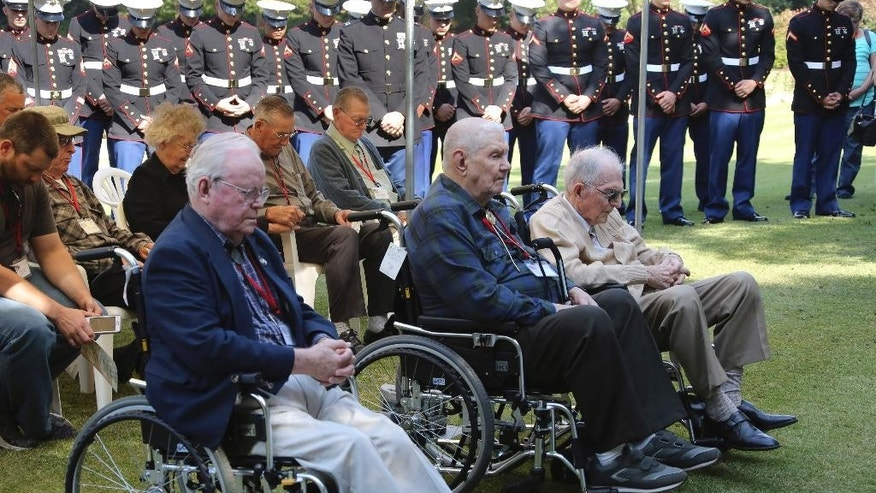 Former American prisoners of war, from left, William Howard Chittenden, 95, of Wheaton, IL., Carl Dyer, 91, of Oglesby, IL., and Joseph Demott, 97, of Lititz, PA., join others to  pray at the Commonwealth War Graves in Yokohama near Tokyo Monday, Oct. 12, 2015. Nine former American POWs were in Japan to revisit some of the places where they were held seven decades ago and recount their memories. The men, all in their 90s, opened the tour Monday with a memorial service for their fellow fallen soldiers at the Commonwealth War Graves. (AP Photo/Koji Sasahara)