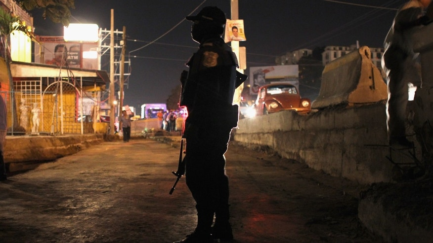 ACAPULCO, MEXICO - MARCH 01:  A federal policeman stands guard at the scene of a suspected drug-related execution on March 1, 2012 in Acapulco, Mexico. Drug violence surged in the coastal resort in the last year, making Acapulco the second most deadly city in Mexico after Juarez. One of Mexico's top tourist destinations, Acapulco has suffered a drop in business, especially from foreign tourists, due to reports of the violence. Toursim accounts for some 9 percent of Mexico's economy and about 70 percent of the output of Acapulco's state of Guerrero.  (Photo by John Moore/Getty Images)