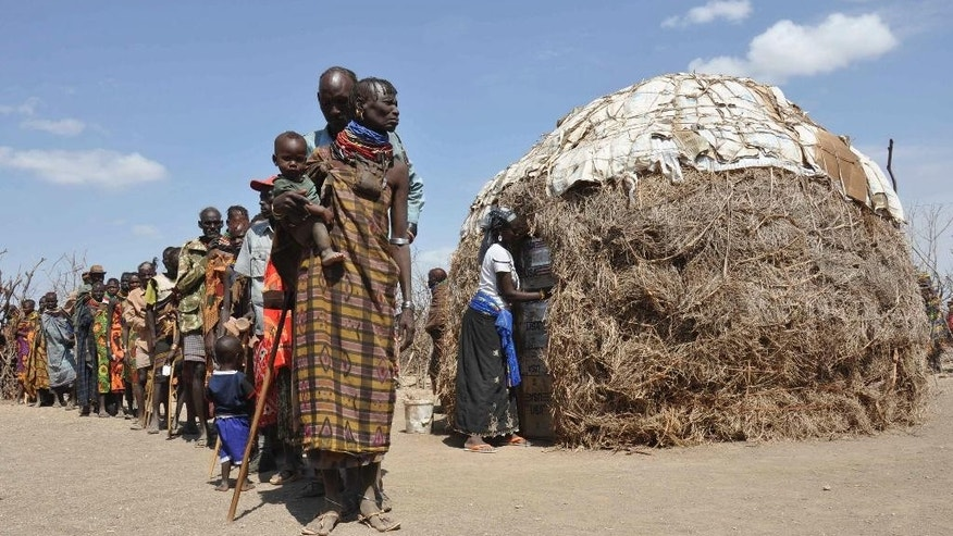 "FILE - In this Tuesday, Aug. 30, 2011 file photo, Turkana people wait in a line to receive food during a famine from Oxfam in central Turkana district, Kenya. Calamitous famines appear to have vanished from the planet, but more must be done to eradicate all such scourges, including redrafting U.S. terror legislation that inhibits life-saving humanitarian work, according to a new report. The study, part of the 2015 Global Hunger Index published Monday, Oct. 12, 2015 says it's one of the ""unheralded achievements"" of the last 50 years: the elimination of calamitous famines that cause more than 1 million deaths, and reduction ""almost to a vanishing point"" of great famines, which cause more than 100,000 deaths. (AP Photo/Tobin Jones, File)"