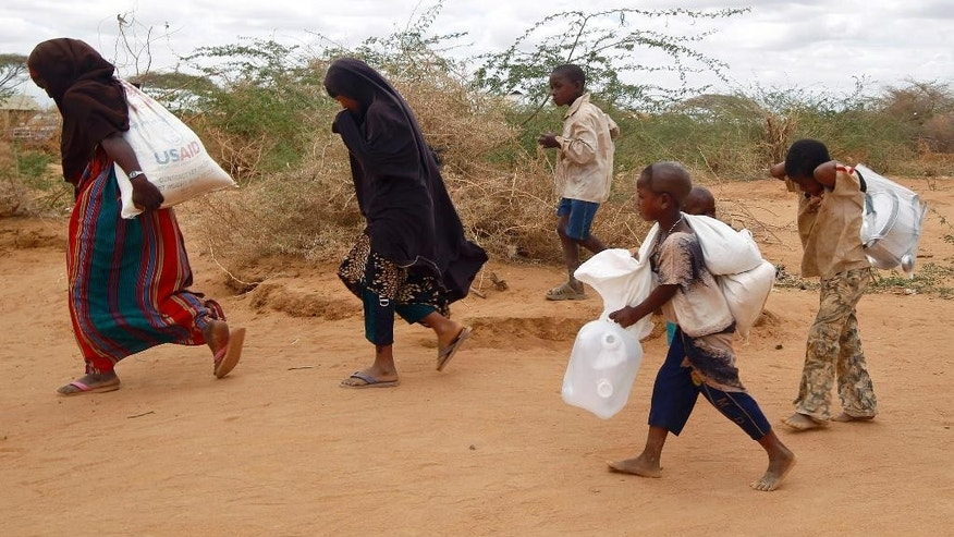 "FILE-- In this Friday Aug. 5 2011 file photo,  newly arrived Somali family carry their supply of aid outside Dadaab, eastern Kenya, 100 kms (60 miles) from the Somali border. Calamitous famines appear to have vanished from the planet, but more must be done to eradicate all such scourges, including redrafting U.S. terror legislation that inhibits life-saving humanitarian work, according to a new report. The study, part of the 2015 Global Hunger Index published Monday, Oct. 12, 2015 says it's one of the ""unheralded achievements"" of the last 50 years: the elimination of calamitous famines that cause more than 1 million deaths, and reduction ""almost to a vanishing point"" of great famines, which cause more than 100,000 deaths. (AP Photo/ Jerome Delay-File)"