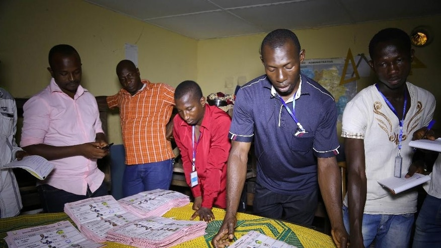 Electoral officials sort out ballot papers at the end of presidential elections in Conakry, Guinea, Sunday, Oct. 11, 2015. Guinea's president and main opposition candidate called for calm Sunday when they voted in the country's presidential election, after days of electoral clashes. (AP Photo/Youssouf Bah)
