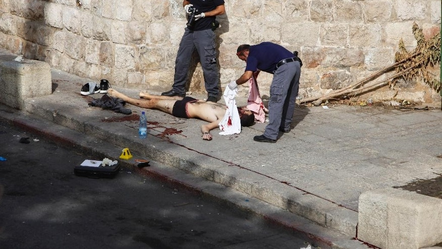 Israeli police officers examine the body of a Palestinian at the scene of a stabbing attack near the Lions Gate of Jerusalem's walled Old City on the predominantly Arab eastern side of Jerusalem, Monday, Oct. 12, 2015. The Palestinian man attacked an Israeli officer with a knife Monday but the officer was wearing a protective vest and was not injured and the attacker was shot dead by police, Israeli police said. In recent weeks, at least 25 Palestinians, including nine attackers, have been killed by Israeli forces, while five Israelis have been killed in attacks. (AP Photo/Mahmoud  Illean)